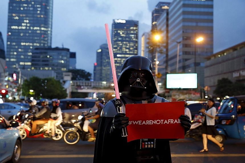 A man wearing a Darth Vader costume making a statement with his placard in Jalan M.H. Thamrin in downtown Jakarta yesterday, near the scene of Thursday's attack.