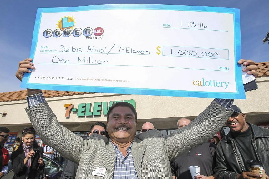 Mr Balbir Atwal, owner of the California 7-Eleven outlet that sold one of the three Powerball winning tickets, holding up a symbolic cheque for US$1 million - his prize from the California State Lottery for selling a jackpot-winning ticket.