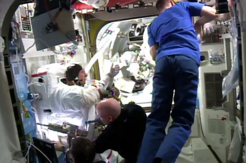 Tim Kopra gets help with his spacesuit back inside the ISS after the spacewalk was called off.