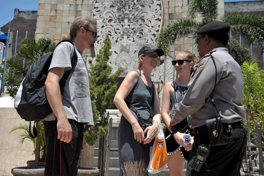 A police officer holds a weapon as he talks with tourists in front of the Bali Bomb Monument in Kuta.