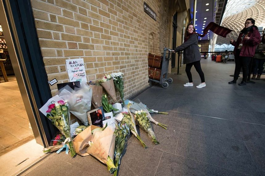 Floral tributes to Rickman at the Platform 9 3/4 Harry Potter display at King's Cross station in London.