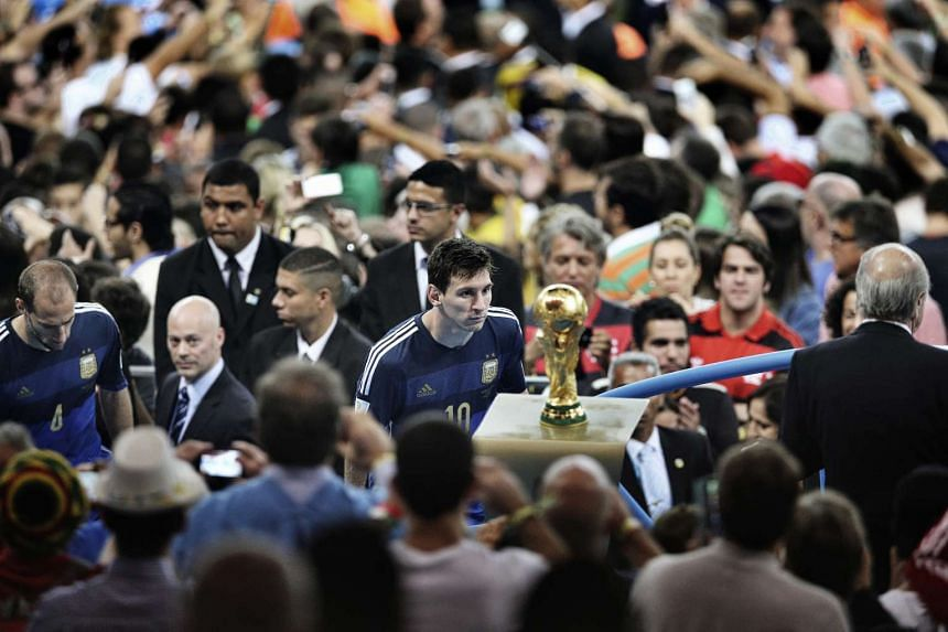 First Prize, Sports Category, Singles. Argentina player Lionel Messi faces the 2014 World Cup trophy during the final celebrations at Maracana Stadium in Rio de Janeiro, Brazil. His team lost to Germany 1-0. Chinese photographer Bao Tailiang captured