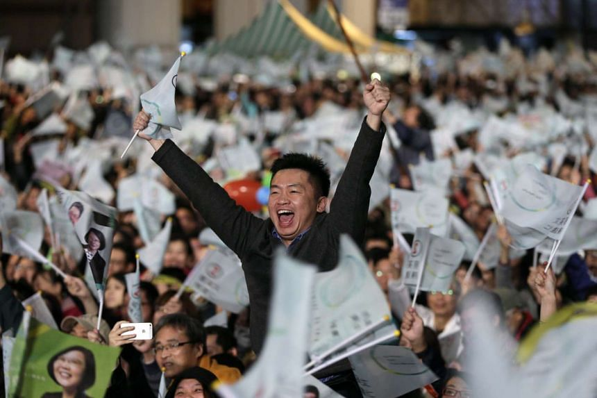 Democratic Progressive Party supporters cheer while watching the vote counting process.