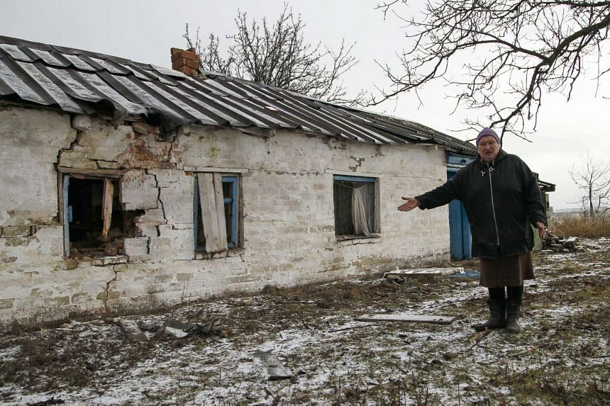A woman stands next to a building damaged by shelling in Kominternovo village, near Mariupol, Ukraine, on Jan 15, 2016.