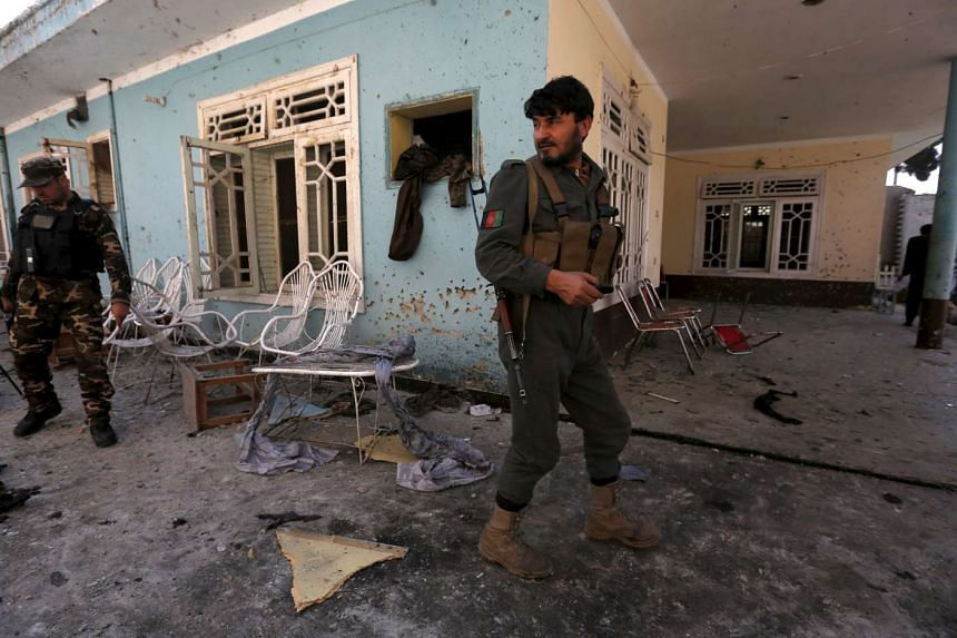 Afghan security forces inspect the site of a suicide attack in Jalalabad, Afghanistan on Jan 17, 2016.