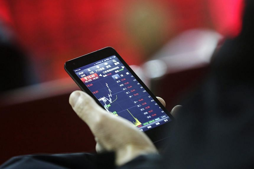 A Chinese investor looks at a mobile phone showing share price developments at a securities brokerage house in Beijing, China, on Jan 14, 2016.