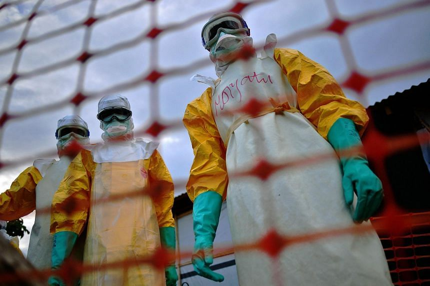Medical staff wearing protective clothing to treat the body of an Ebola victim at their facility in Kailahun.