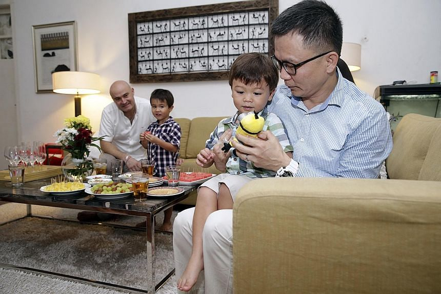 Dr Low Lee Yong hands Adam a toy as Mr Christophe Cabibel and older son Louis look on. Adam had suffered a febrile fit while on a flight back from France and passed out. Dr Low attended to and revived him. The Cabibels met Dr Low yesterday at their P