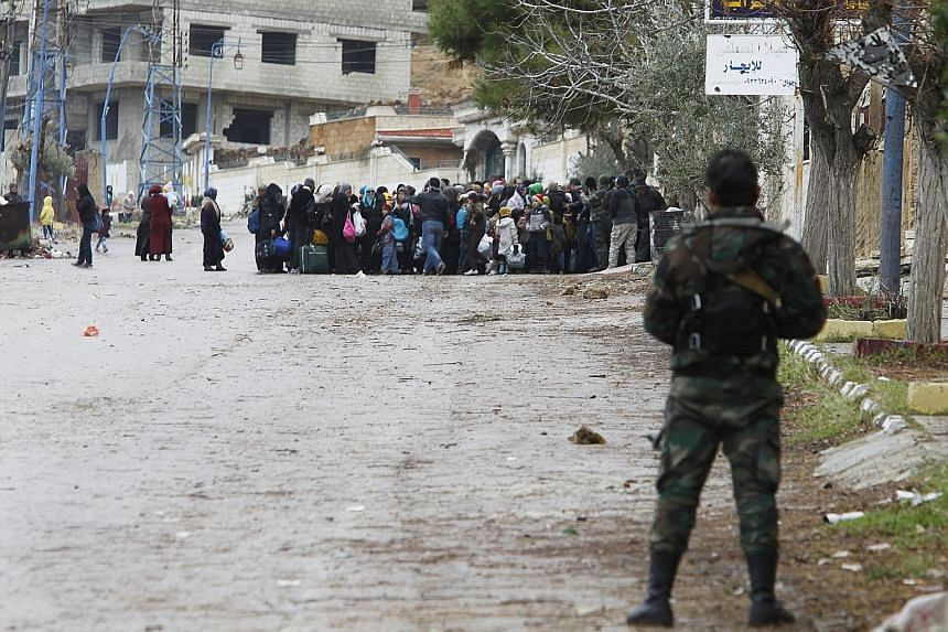 Syrian soldiers monitoring residents who said they had received permission from the government to leave Madaya after an aid convoy entered the besieged town last Thursday.