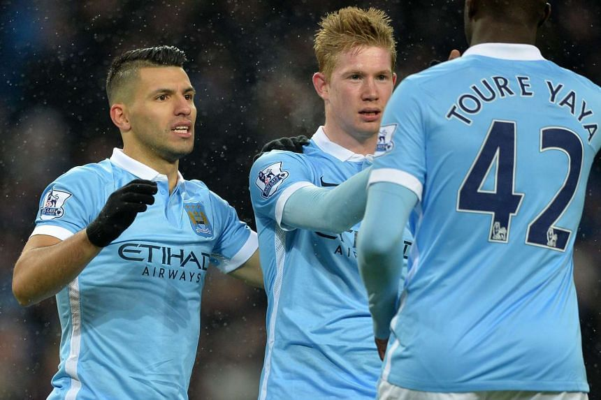 Manchester City's Aguero (left) celebrates with Kevin De Bruyne (centre) and Yaya Toure after scoring his team's third goal.