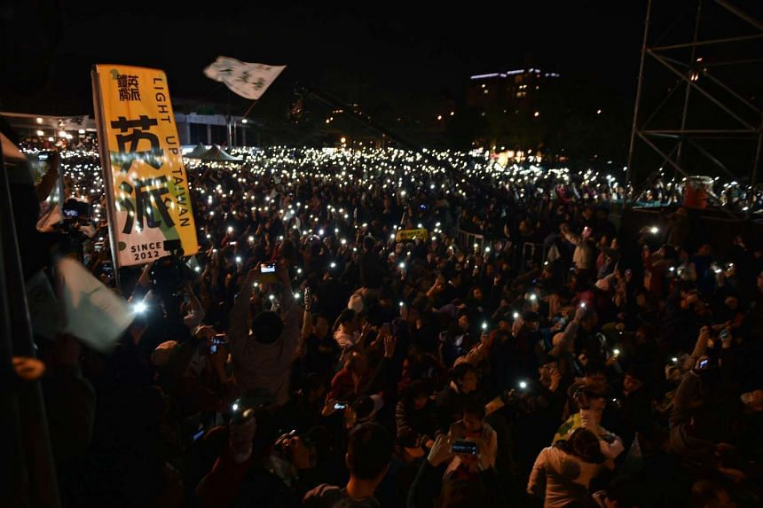 Democratic Progressive Party (DPP) supporters holding up their mobile phones outside the party headquarters as they anticipate an election victory for Ms Tsai Ing-wen. The DPP swept to a landslide victory by capturing 68 seats, compared with the 35 w