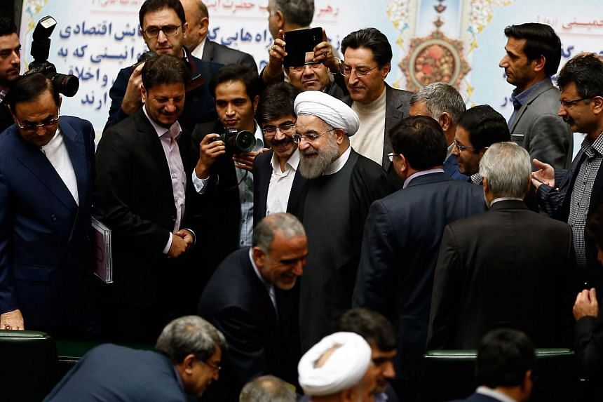 Parliament members congratulate Iranian President Hassan Rouhani (centre) after some international sanctions against Iran were lifted.