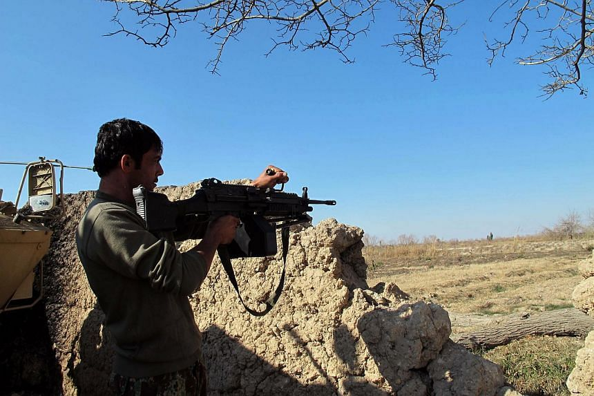 An Afghan National Army (ANA) soldier keeps watch during an ongoing battle with Taliban militants in the Nad Ali district of Helmand on Dec 22, 2015.