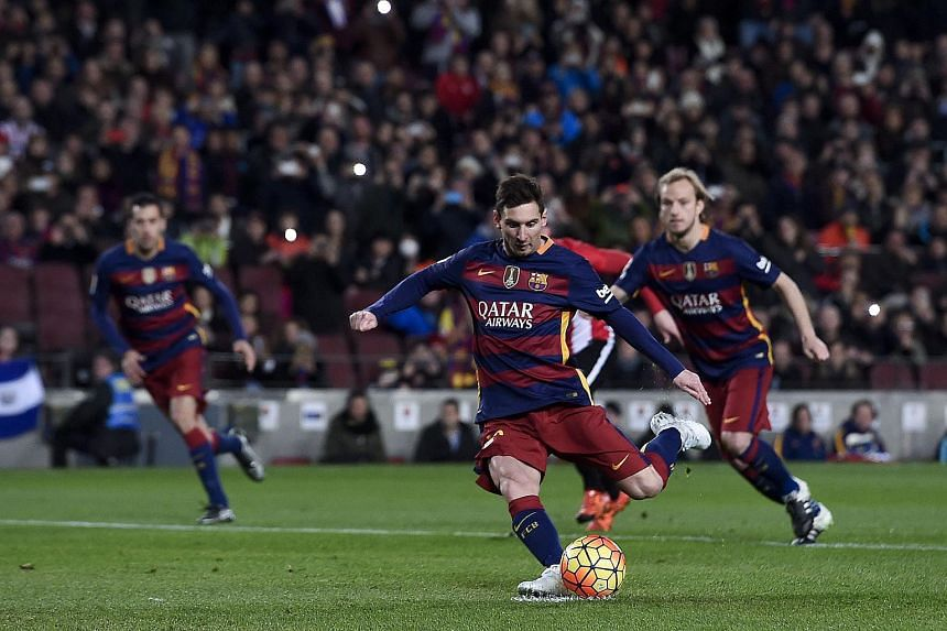 Lionel Messi scores on a penalty kick during the Spanish league football match between FC Barcelona and Athletic Club Bilbao.