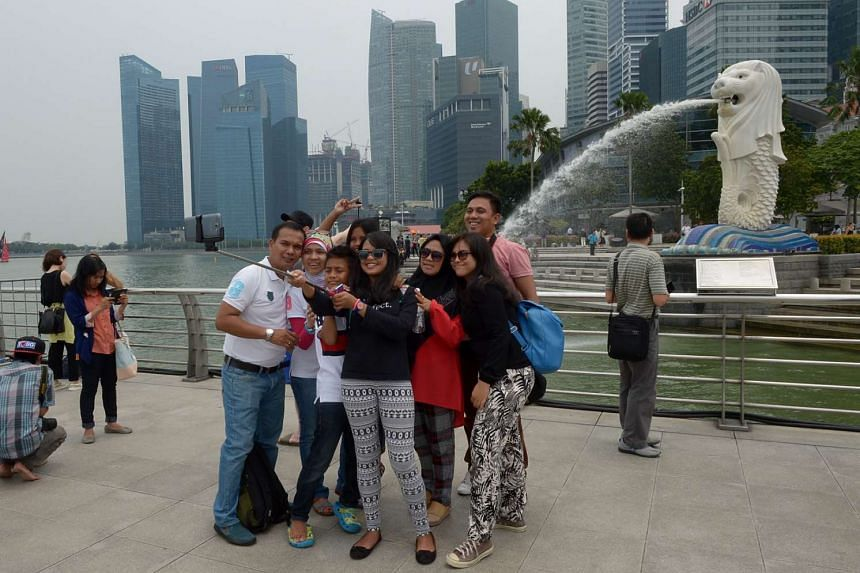 Tourists taking pictures in front of the Merlion on Sept 17, 2015.