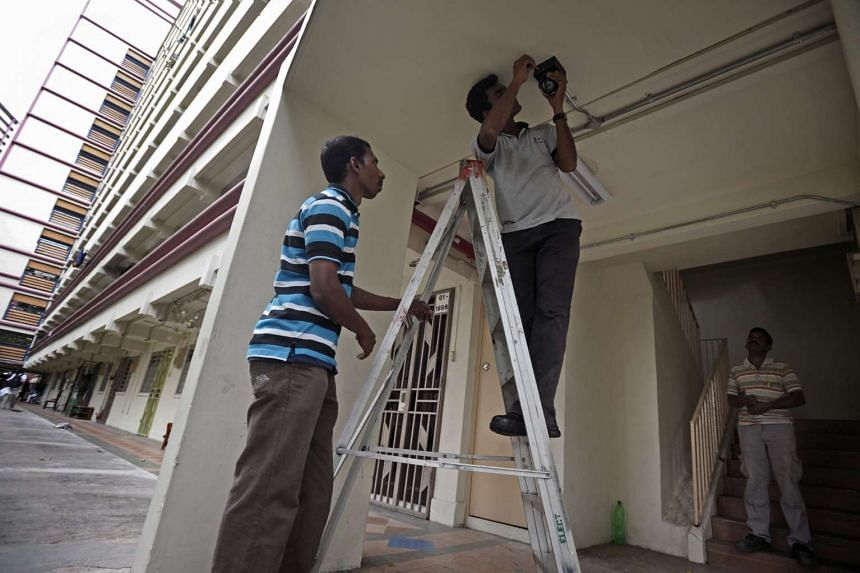 A CCTV camera being installed at the foot of a stairwell at an HDB block in Jalan Bukit Merah.