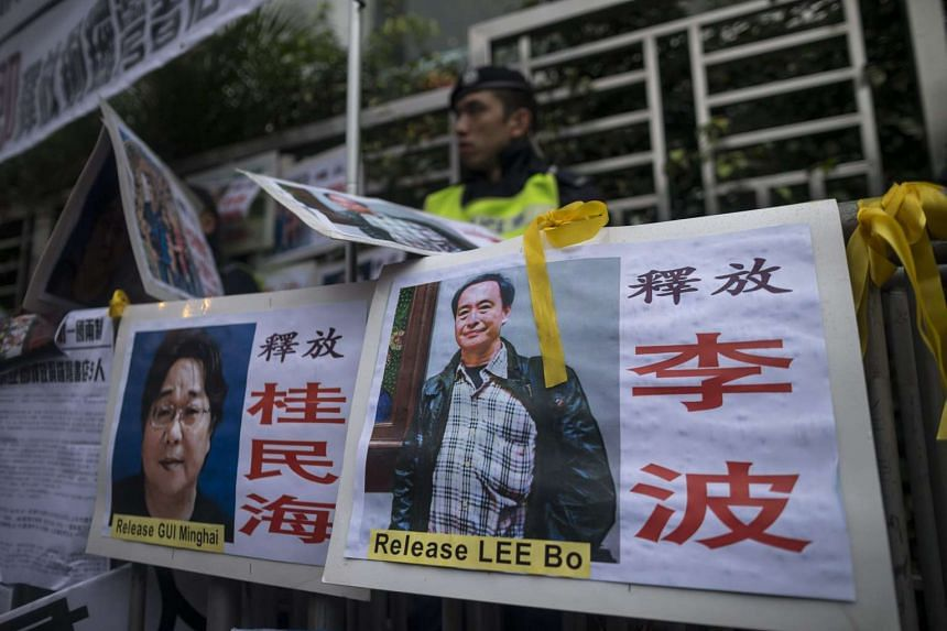 Photographs of the missing bookstore shareholders Gui Minhai (left) and Lee Bo outside the China Liaison Office during a protest in Hong Kong.