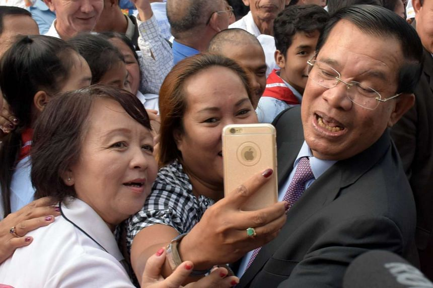This photo taken on January 7, 2016 shows Cambodian Prime Minister and president of the Cambodian People's Party (CPP) Hun Sen (right) posing for a selfie with supporters during a CPP ceremony marking the 37th anniversary of the fall of the Khmer Rou