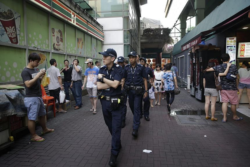 Policemen patrolling the area outside People's Park Complex, Singapore.