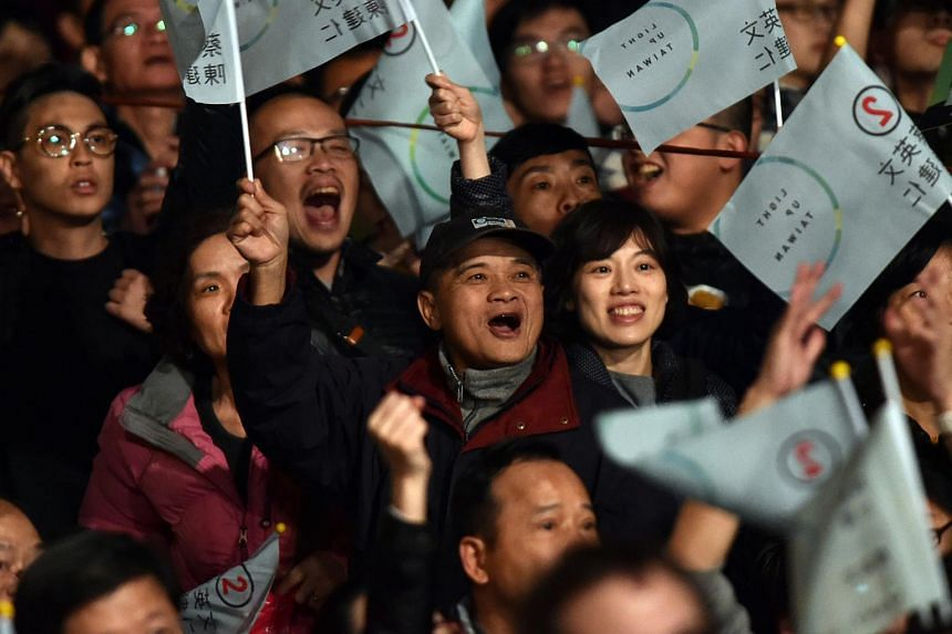 Supporters of Taiwan President-elect Tsai Ing-wen wave campaign flags in Taipei on Jan 16, 2016.