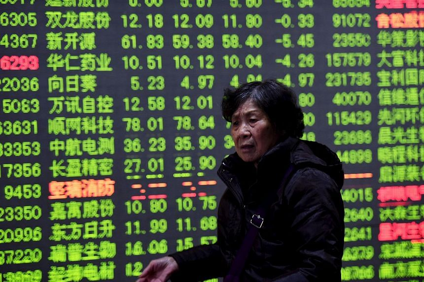 An investor walks past an electronic screen showing stock information at a brokerage house in Hangzhou, China, Jan 15, 2016.