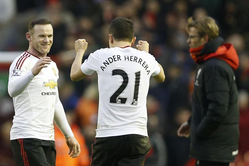 Manchester United's Wayne Rooney (left) celebrates at full time with Ander Herrera (centre) as Liverpool's manager Juergen Klopp looks on.