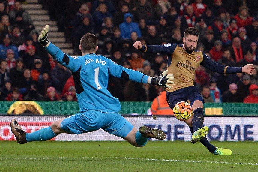 Stoke City's English goalkeeper Jack Butland (left) jumps to save a shot from Arsenal's French striker Olivier Giroud.