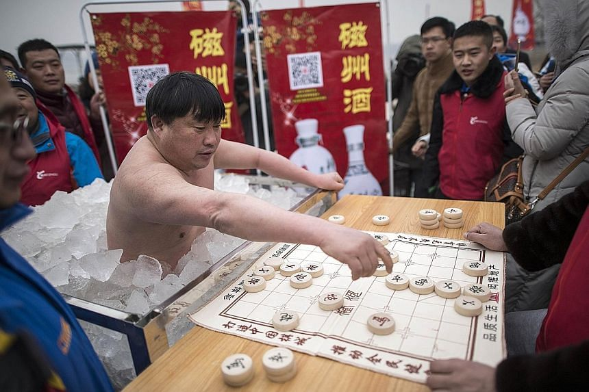 """Mr Cui, known as the """"Polar Bear of Huangshan"""", playing Chinese chess while half-submerged in a box of ice. He began competing in such cold endurance contests around a decade ago."""