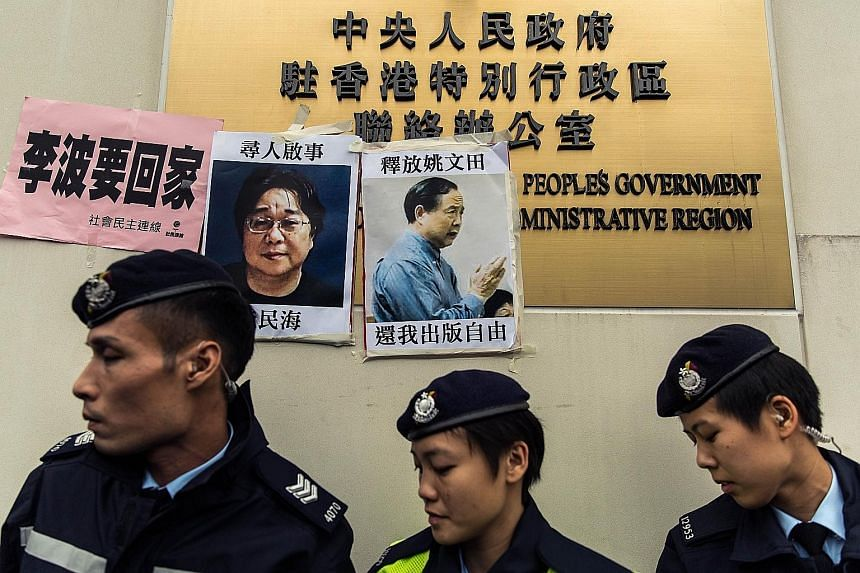 Hong Kong police in front of missing-person notices for Mr Gui Minhai (left), one of five missing booksellers linked to the Mighty Current publishing house, and Hong Kong publisher Yao Wentian (right), who had been planning to release a book critical