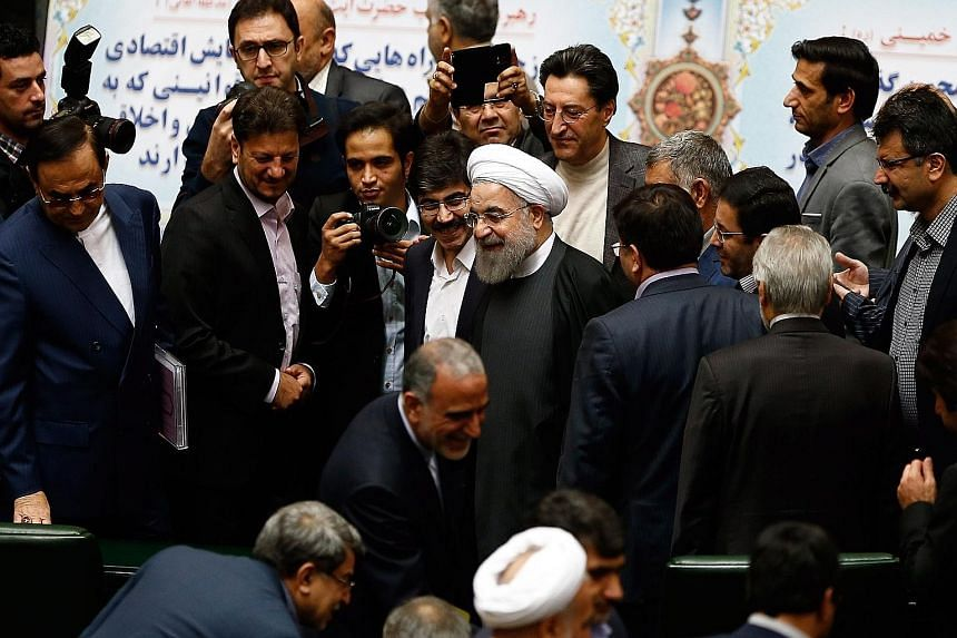 MPs congratulating Mr Rouhani (centre) yesterday during a parliamentary session on the Budget after some international sanctions against Iran were lifted.