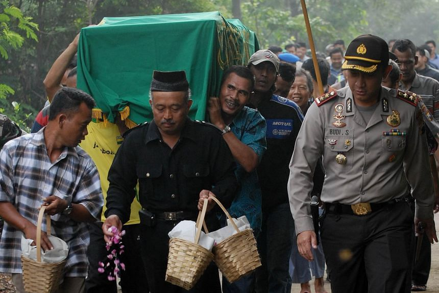 An armed police officer accompanying mourners during the funeral procession of terror attack victim Rico Hermawan at a cemetery in Boyolali, Indonesia's central Java island, yesterday. The death toll from last Thursday's attack has risen to eight, af