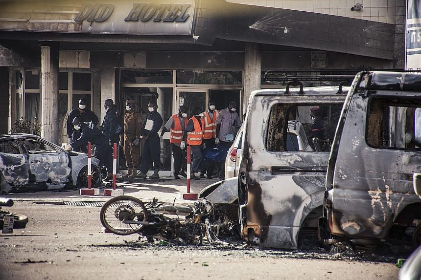Investigators carrying a body bag out of the Splendid Hotel in Burkina Faso's capital Ouagadougou. One survivor, a French architect known only as Ludovic, said he saw three assailants singling out white victims before running into the Splendid Hotel.