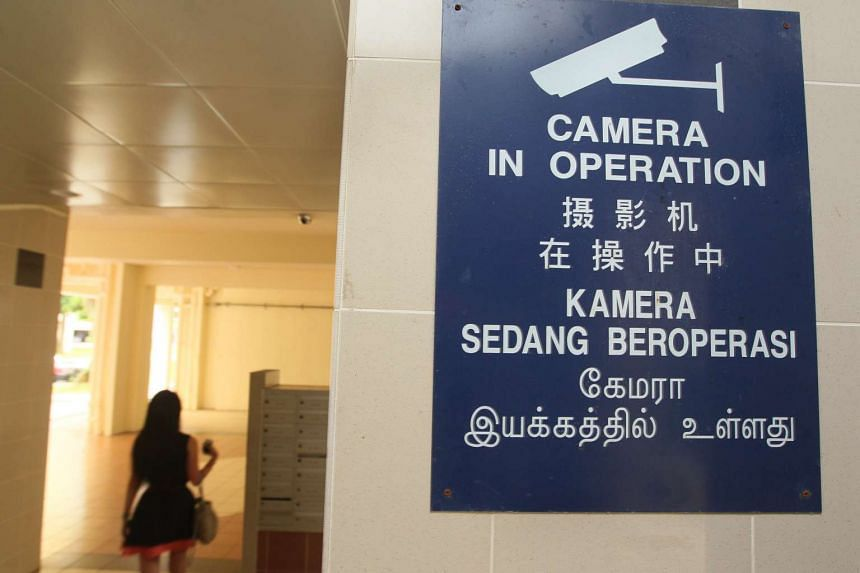 """A """"Camera In Operation"""" sign at the lift lobby of a block in Woodlands Drive."""