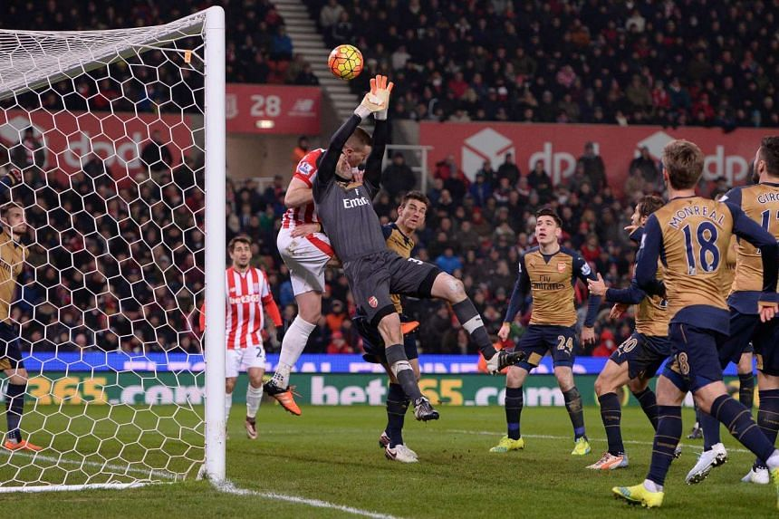 Arsenal's Czech goalkeeper Petr Cech (centre) jumps to make a save during the EPL match against Stoke City at the Britannia Stadium in Stoke-on-Trent on Sunday, Jan 17.