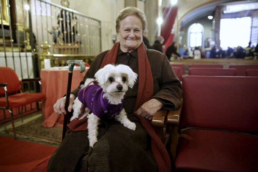 A woman holds her dog as she waits for a mass in San Anton Church in Madrid on Sunday, Jan 17.