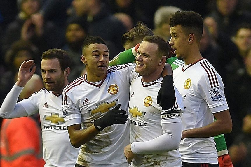 Manchester United's Wayne Rooney (centre-right) is congratulated by Jesse Lingard (centre-left) after winning the EPL match over Liverpool at Anfield Sunday, Jan 17.