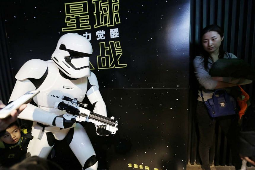 A boy hides behind a life size Stormtrooper figure as movie goers arrive for the first screening of Star Wars: The Force Awakens in Beijing on Jan 9.