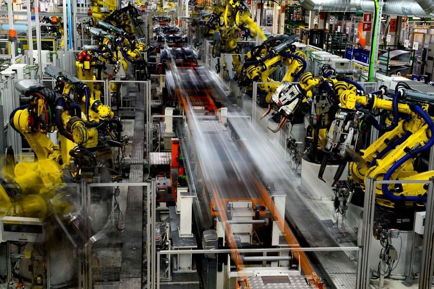Robots work on Seat Leon vehicles at Volkswagen AG's Seat automobile plant in Spain, on July 15, 2014.