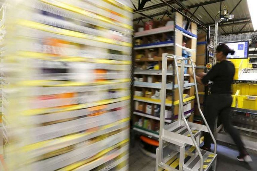 An employee pulls items out of robotically controlled bins at the Amazon Fulfillment Center on Nov 29, 2015.