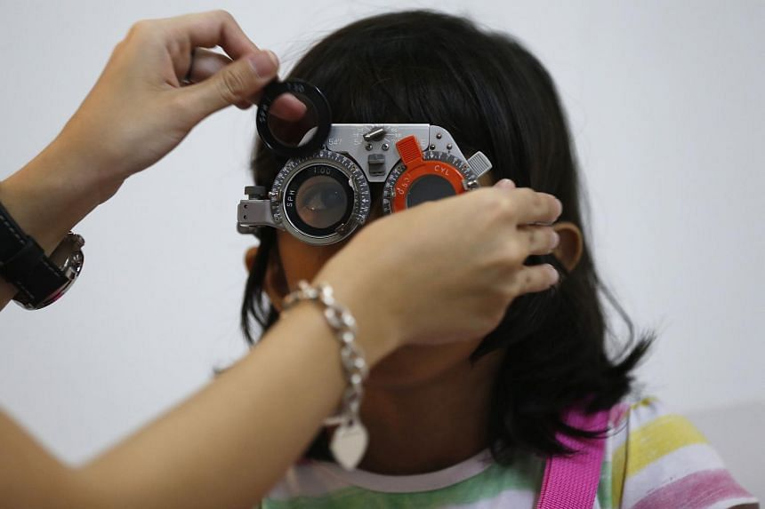 A girl getting her eyes checked for myopia.