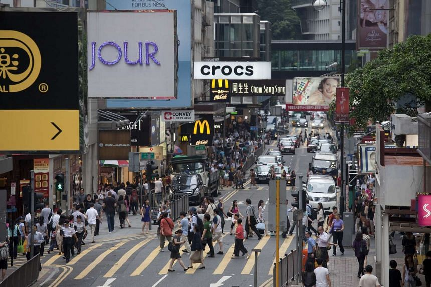 Pedestrians crossing Queen's Road in the Central district in Hong Kong, China.