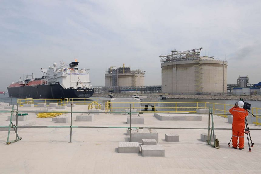 A ship bearing Liquefied Natural Gas (LNG) and the two tanks at Singapore's first LNG terminal.