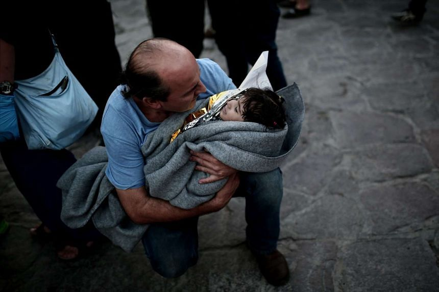 A refugee holds a child after arriving on the Greek Island of Lesbos.