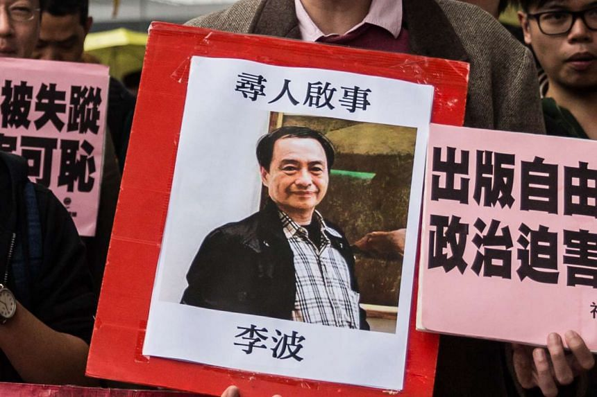 A protestor holds up a missing person notice for Lee Bo at China's Liaison Office in Hong Kong on Jan 3, 2016.