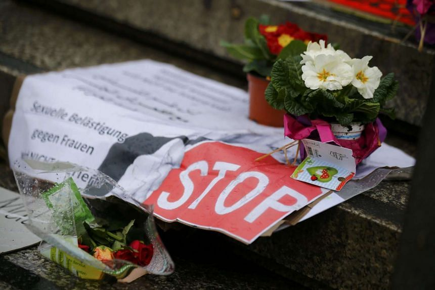 """A sign reading """"Sexual harassment against women will NOT be tolerated"""" and flowers are placed in a square in Cologne, Germany, on Jan 11, 2016."""