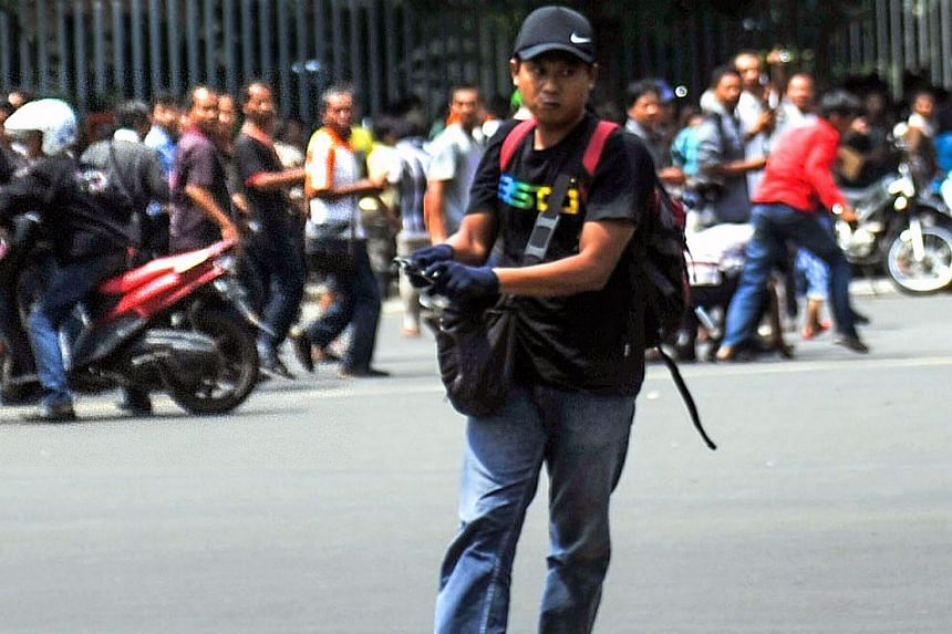 The militant Afif carrying his weapon on the street during attacks in Jakarta on Jan 14.
