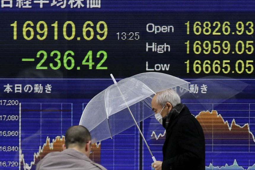 Pedestrians walking past a display showing stock prices in Tokyo on Jan 18.