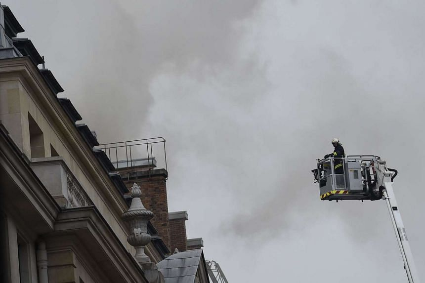 A firefighter prepares to reach the site of a fire at the Ritz Hotel in Paris on Jan 19, 2016.