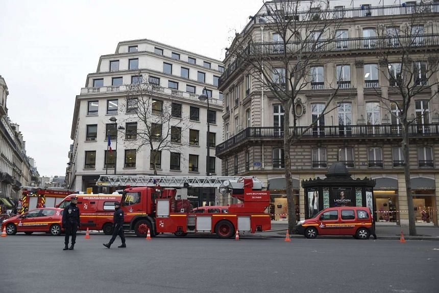Police officers stand guard next to fire trucks parked near the Ritz Hotel on Jan 19. 2016.