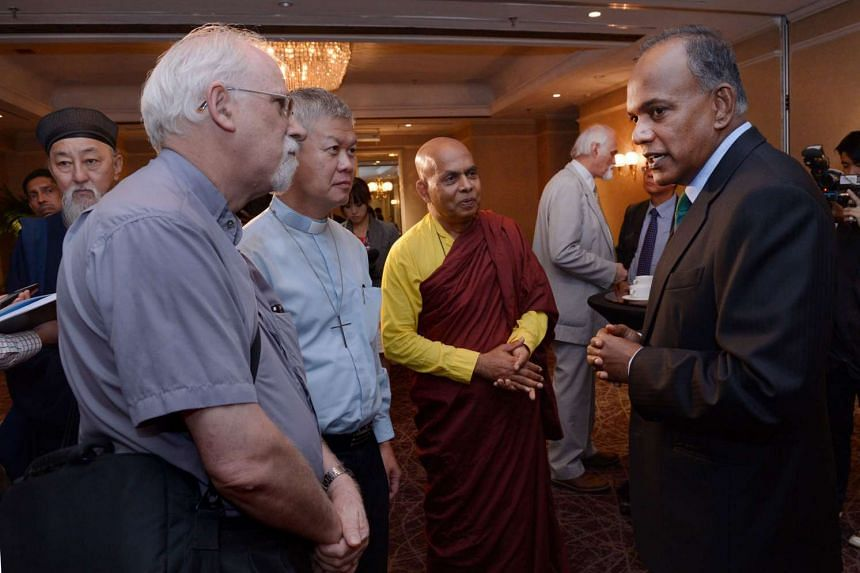 Mr K Shanmugam (right) chatting with religious leaders at the Marina Mandarin Hotel on Jan 19, 2016.